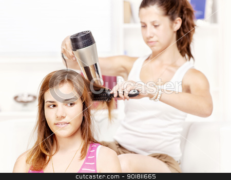 Teenage girl dries hair to her friends stock photo, Teenage girl dries hair to her friends at home by iMarin