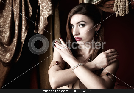 Attractive Belly Dancer stock photo, Attractive belly dancer with crossed arms and arabesque background by Scott Griessel
