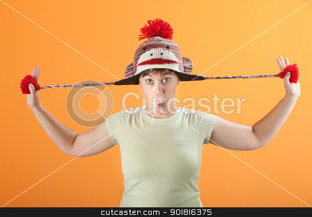Woman Plays with Hat stock photo, Young Caucasian woman plays with her sock monkey cap by Scott Griessel