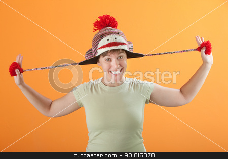 Woman Pulling Her Hat stock photo, Young Caucasian lady in a playful mood stretching her hat by Scott Griessel