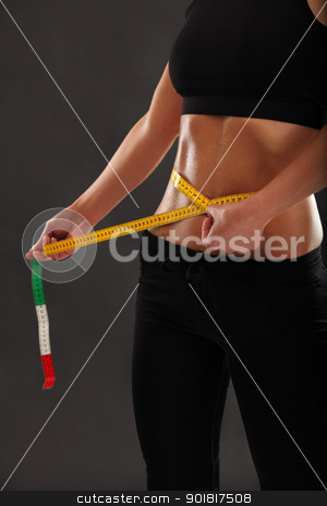 Measuring her slim waist stock photo, Photo of a tanned slim young woman measuring her sweaty waistline over dark background. by © Ron Sumners