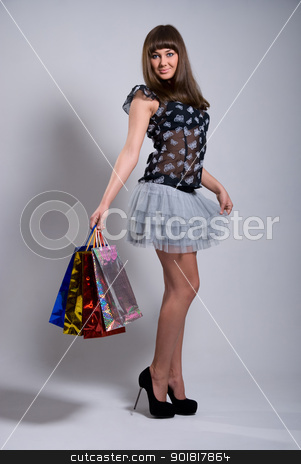 studio portrait of a beautiful young woman stock photo, studio portrait of a beautiful young woman, in a colourful outfit, holding in her hands a few shopping bags by Vadim