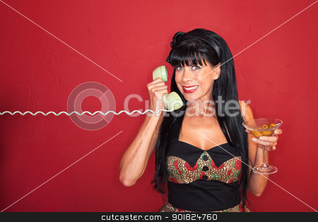 Excited Woman On Phone Call stock photo, Smiling middle-aged woman on phone with a martini by Scott Griessel