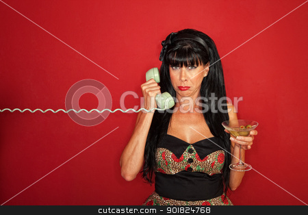 Upset Woman On Phone Call stock photo, Upset Caucasian lady on phone with martini over maroon background by Scott Griessel
