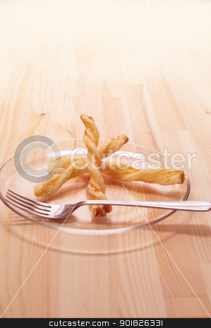 puff pastry sticks stock photo, puff pastry sticks on a glass transparent plate over pine wood table by Francesco Perre