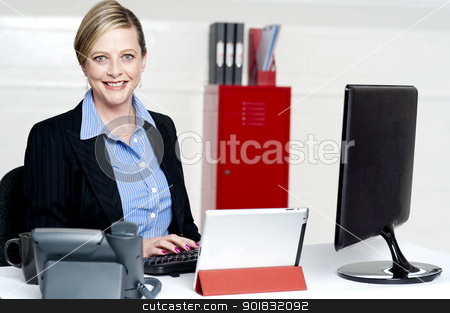 Cheerful female secretary typing document stock photo, Cheerful female secretary typing document on computer. Working in office by Ishay Botbol   