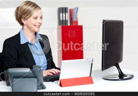 Confident businesswoman working in office stock photo, Confident businesswoman working in office. Concentration on computer screen while typing doucment by Ishay Botbol