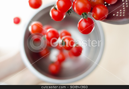 Cherry Tomatoes Tumbling From Metal Colander Into Metal Pan stock photo, Ripe cherry tomatoes being tumbled and poured down from a metal colander into a silver metal pot with white background. by TheFull360