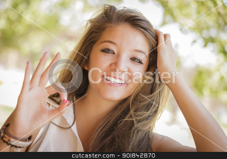 Attractive Mixed Race Girl Portrait with Okay Hand Sign Outdoors stock photo, Attractive Smiling Mixed Race Girl Portrait with Okay Hand Sign Outdoors. by Andy Dean