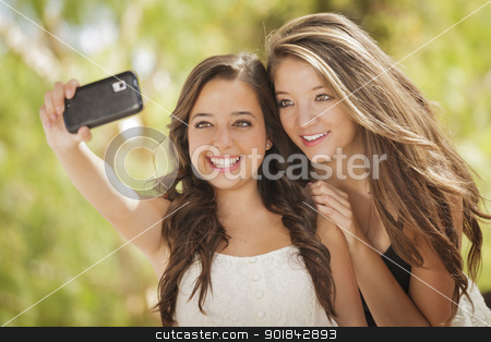 Attractive Mixed Race Girlfriends Taking Self Portrait with Came stock photo, Two Attractive Mixed Race Girlfriends Taking Self Portrait with Their Phone Camera Outdoors. by Andy Dean
