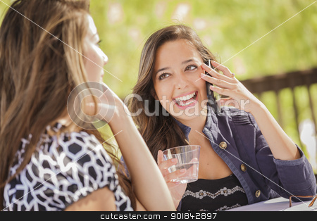 Mixed Race Girls Talking on Thier Mobile Cell Phones stock photo, Mixed Race Girls Talking on Thier Mobile Cell Phones Sitting Outside at a Table. by Andy Dean