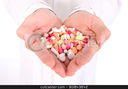 Bunch of meds stock photo, Young doctor is offering to you bunch of different pills as medication for your good health isolated on the white background (shalow dept) by vaximilian