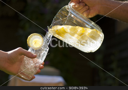 Pouring homemade lemonade into glass stock photo, Mans hand and forearm pouring homemade lemonade froma glass jug of lemons and water, into a glass with lemon slice, held by younger youths hand in sunshine. by TheFull360