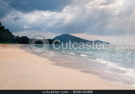 Storm clouds under tropical sandy coast stock photo, Heavy storm clouds and sunbeams under tropical sandy sea coast with clear blue water by Iryna Rasko