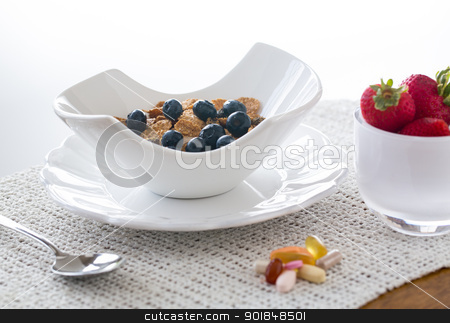 Breakfast of bran flakes blueberries stock photo, Breakfast of blueberries, bran flakes strawberries in modern pottery bowl by Steven Heap