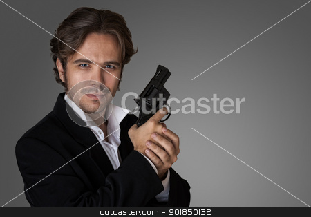 a man with a gun stock photo, a man with a gun in the hands of the studio on a gray background by miloslav78