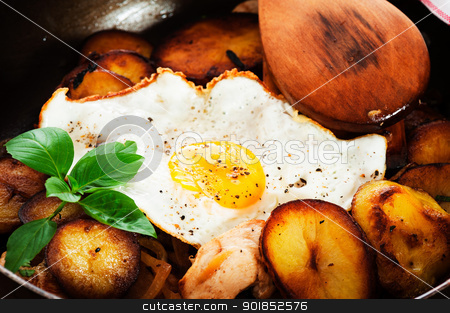 fried potatoes stock photo, fried potatoes onion chicken and fried egg in a pan on a wooden table by p.studio66