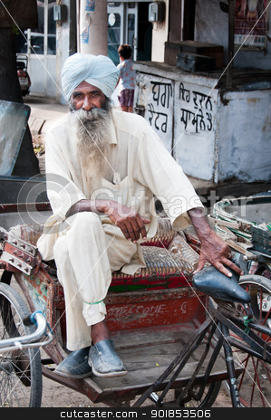 Senior rickshaw is waiting for passengers stock photo, Amritsar, India - August 26, 2011: Rickshaw is a traditional asian taxi. Senior rickshaw is sitting on his cycle by Iryna Rasko