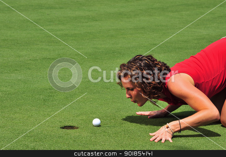 The Last Inch stock photo, A pretty lady golfer attempts to blow a ball into the hole with a breath of air by Jim Fitzroy