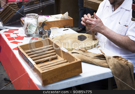 Rolling cigars stock photo, Man hand rolling cigars on the street by Abdul Sami Haqqani