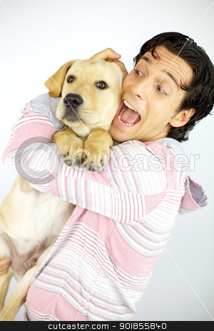Young cool man plays with puppy dog labrador stock photo, happy young male model hugging puppy labrador dog  by federico marsicano