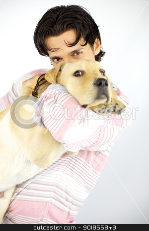 Young man kissing his puppy dog labrador stock photo, Cool male model happy loving his dog labrador by federico marsicano