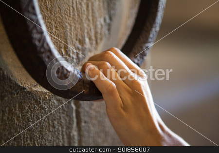 Woman knocking on a clapper stock photo, A woman is knocking on an old metal clapper by Dario Rota