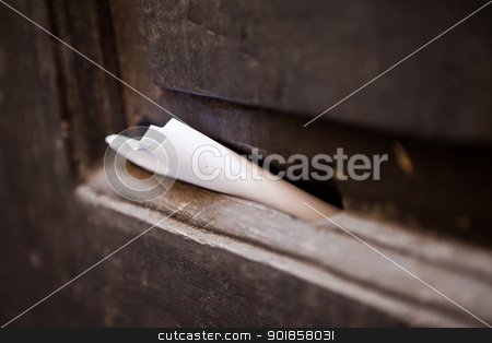 Letter in old mail slot stock photo, Paper inside a brown wooden old mail slot by Dario Rota
