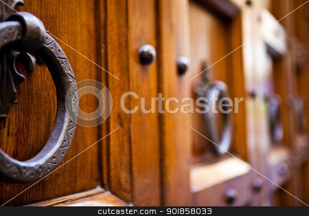 Metal clapper on ancient wooden door stock photo, Four metal calppers on an old brown door by Dario Rota