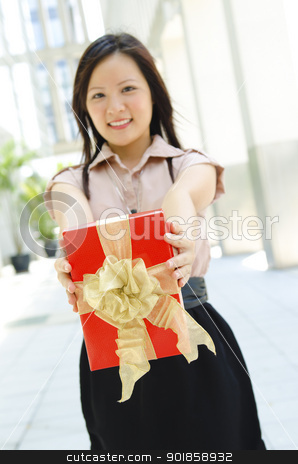 Gift for you stock photo, Young Asian girl arms out holding a beautiful wrapped present. Focus is on the ribbons. by szefei