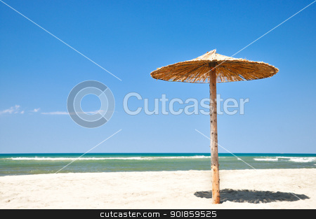 Umbrella on beach stock photo, Tropical straw umbrella on a beautiful sand beach by zagart