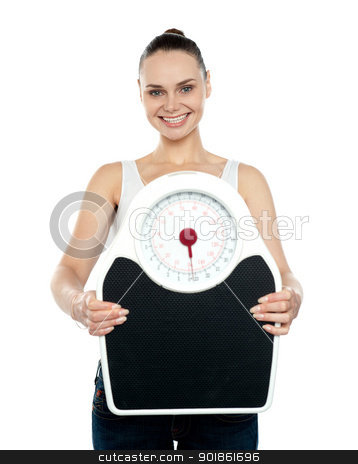 Cheerful young woman holding a weighing stock photo, Portrait of cheerful young woman holding a weighing scale against white background by Ishay Botbol