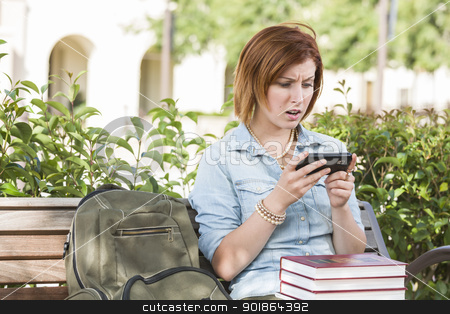 Stunned Young Female Student Outside Texting on Cell Phone stock photo, Stunned Young Pretty Female Student Outside with Backpack and Books Sitting on Bench Texting on Cell Phone. by Andy Dean