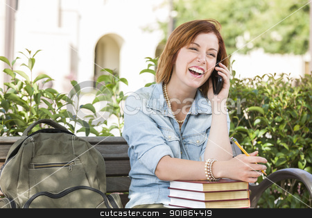 Young Female Student Outside Using Cell Phone Sitting on Bench stock photo, Smiling Young Pretty Female Student Outside on Cell Phone with Backpack and Books Sitting on Bench. by Andy Dean