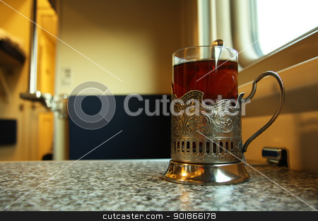 Travel in train with a glass of hot tea stock photo, Traditional train cup with hot tea in a sleeper train wagon, Russia by Yulia Zhukova