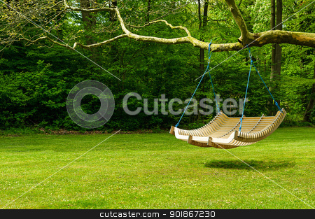 Swing bench in lush garden stock photo, Curved swing bench hanging from the bough of a tree in a lush garden with woodland backdrop for relaxing on those hot summer days by Instudio 68