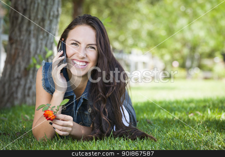 Mixed Race Young Female Talking on Cell Phone Outside stock photo, Attractive Happy Mixed Race Young Female Talking on Cell Phone Outside Laying in the Grass. by Andy Dean