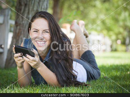 Mixed Race Young Female Texting on Cell Phone Outside stock photo, Attractive Happy Mixed Race Young Female Texting on Her Cell Phone Outside Laying in the Grass. by Andy Dean