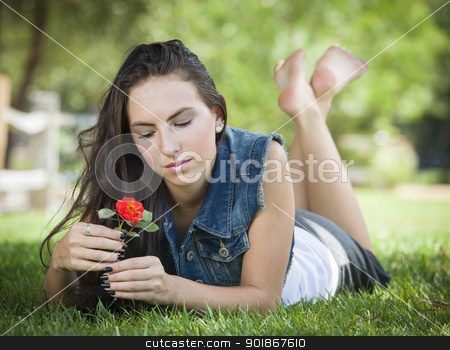 Attractive Mixed Race Girl Portrait Laying in Grass stock photo, Attractive Mixed Race Girl Daydreaming Laying in Grass Outdoors with Flower. by Andy Dean