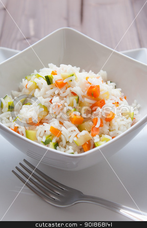 Basmati Rice with veggies stock photo, Basmati rice with carrots and courgettes in a dish on wood table by Giordano Aita