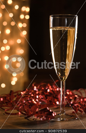 Flute of hampagne. stock photo, Champagne flute among red ribbons, defocused lights background. by Piotr Skubisz