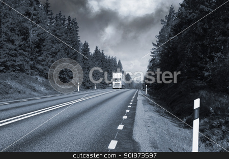 trucking on small country freeway stock photo, truck driving on smaller country freeway, trees and forrest, dark clouds approaching, blue toning concept by lagereek
