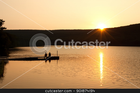 Sunset at the Lake stock photo, A couple sitting on a boat dock watching reflections on as the sun sinks over the mountain. by Delmas Lehman