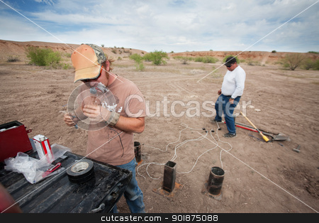 Special Effects Team Working stock photo, Special effect team setting up pyrotechnics outdoors in desert by Scott Griessel