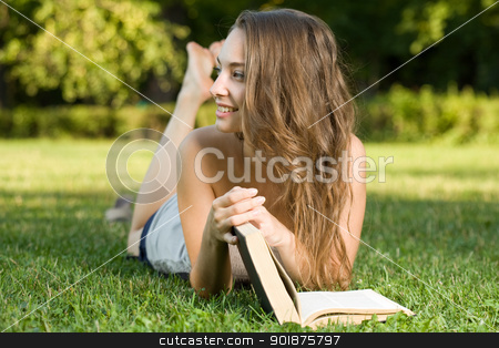 Cute young brunette in the park reading. stock photo, Portrait of a cute young brunette student in the park having fun reading a book. by exvivo