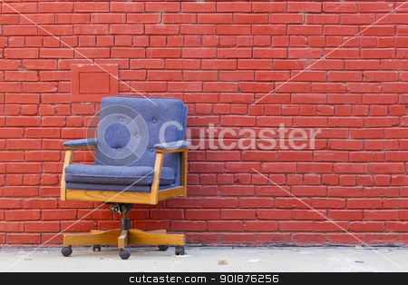 Lonely Office Chair stock photo, Office chair outside against a red brick wall by Walter Arce