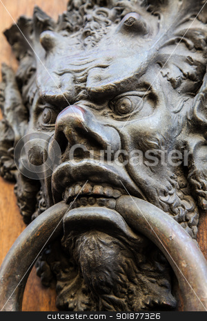 Devil Head Door Knocker stock photo, Door knoker on an old wooden door in Tuscany - Italy by Perseomedusa