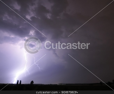 Lightning strikes near a tree stock photo, Lightning strikes at the horizon near two trees. by Volker Pape