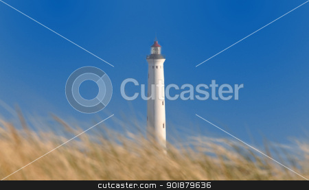 white lighthouse stock photo, A white lighthouse behind a dune. by Volker Pape