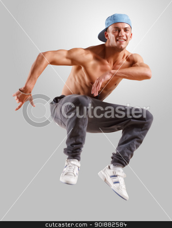 young man dancing hip hop stock photo, young man in a blue cap dancing hip hop by Sergey Nivens